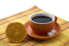Kop van koffie met een sinaasappel stock foto's