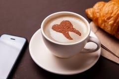Kop van koffie met een tand op het schuim De koffie bederft tanden en maakt hen geel Ochtendkoffie of koffiepauze met croissant royalty-vrije stock afbeeldingen