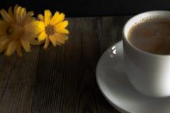 Kop van koffie met gele bloemen op de achtergrond Stock Foto's