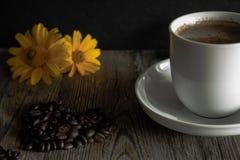 Kop van koffie met gele bloemen op de achtergrond Stock Foto