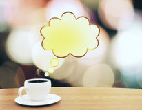 Kop van koffie met gele speachbubble op houten lijst Royalty-vrije Stock Fotografie