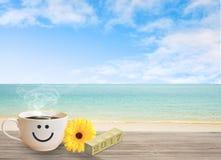 Kop van koffie met gelukkig gezicht op zandstrand over blauwe hemel Stock Fotografie