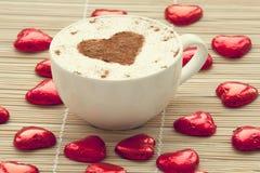 Kop van koffie met hart rond symbool en suikergoed. Royalty-vrije Stock Foto