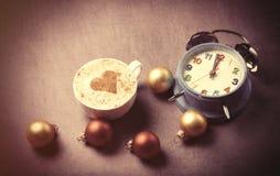 Kop van koffie met hartvorm dichtbij wekker Royalty-vrije Stock Foto's