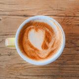 Kop van koffie met het schuim van het hartpatroon in een blauwe kop op rustiek w Stock Fotografie
