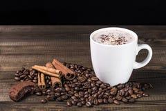Kop van koffie met koffiebonen, koekje en kaneel op houten lijst Royalty-vrije Stock Foto's