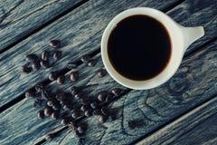 Kop van koffie met koffiebonen op hoogste menings houten achtergrond Stock Fotografie