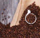 Kop van koffie met koffiebonen tegen houten achtergrond wordt gevuld die Royalty-vrije Stock Afbeeldingen