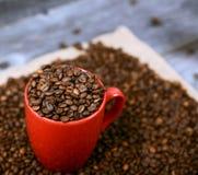 Kop van koffie met koffiebonen tegen houten achtergrond wordt gevuld die Stock Afbeelding