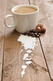 Kop van koffie met melk en hazelnoot Stock Afbeelding
