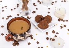 Kop van koffie met melk, koffiebonen, suikergoed, kaarsen, pijpjes kaneel royalty-vrije stock afbeeldingen