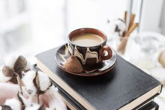 Kop van koffie met melk op de boeken dichtbij het venster, een twijg van katoen royalty-vrije stock foto