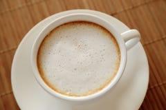 Kop van koffie met melkschuim op houten die lijst vanaf bovenkant wordt gezien Stock Foto's