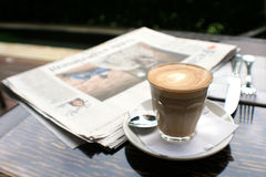 Kop van koffie met nieuwsdocument op lijst Royalty-vrije Stock Afbeeldingen