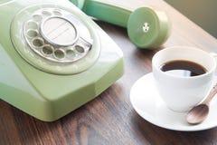 Kop van koffie met oude groene telefoon op houten lijst, Retro stijl Royalty-vrije Stock Fotografie
