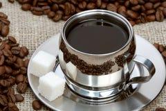Kop van koffie met stuksuiker en bonen royalty-vrije stock afbeeldingen