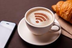 Kop van koffie met WiFi-teken op schuim Vrije toegangspunt aan Internet WiFi Ik houd van koffiepauze met croissant royalty-vrije stock foto's