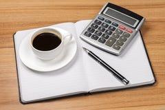 Kop van koffie, notitieboekje, calculator en pen hoogste mening Stock Foto's