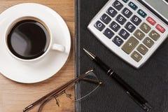 Kop van koffie, notitieboekje, glazen, calculator en pen hoogste mening Stock Afbeeldingen