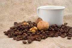 Kop van koffie, okkernoten, koffiebonen en chocolade royalty-vrije stock afbeeldingen