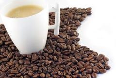 Kop van koffie op coffeebeans die op wit wordt geïsoleerdv Stock Fotografie