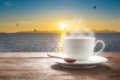 Kop van koffie op een houten lijst op zee mening Stock Foto's