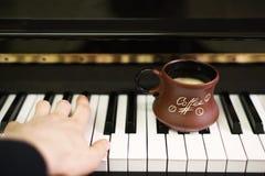 Kop van koffie op een oud pianotoetsenbord terwijl het samenstellen Avondtijd en sommige zonstralen Koffiemok op het pianotoetsen Royalty-vrije Stock Fotografie