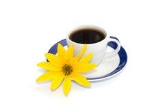 Kop van koffie op een schotel met een blauwe grens en een gele bloem Stock Foto's