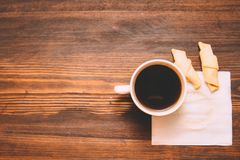 Kop van koffie op een wit servet met koekjes op een houten achtergrond stock afbeeldingen