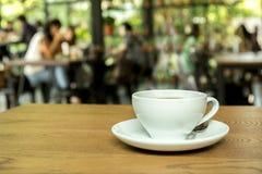 Kop van koffie op houten lijst met onduidelijk beeldachtergrond Stock Fotografie