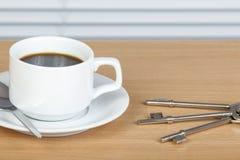 Kop van koffie op lijst met een reeks sleutels Royalty-vrije Stock Afbeeldingen