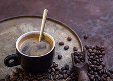Kop van koffie op rustieke achtergrond met koffie rond bonen Royalty-vrije Stock Afbeeldingen