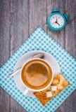 Kop van koffie op schotel met lepel Blauwe servet en wekker stock fotografie