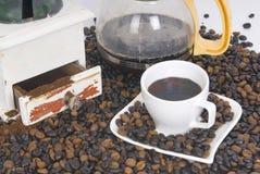 Kop van koffie over koffieboon en koffiepot Royalty-vrije Stock Foto's