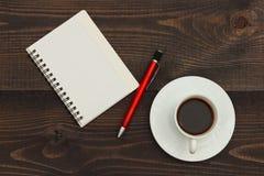 Kop van koffie, pen en notitieboekje op houten Desktop Mening van hierboven stock foto's