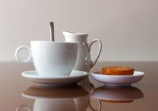 Kop van koffie, roomkankruik en muffin op weerspiegelende lijst Stock Afbeelding