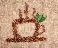 Kop van koffie van bonen met bladeren op juteachtergrond Stock Afbeelding