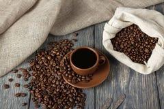 Kop van koffie, zak van koffiebonen op houten oppervlakte Stock Afbeelding