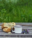 Kop van melk met brood en bloembos Stock Afbeeldingen