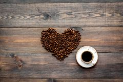 Kop van vers gebrouwen koffie met een volle smaak dichtbij bonen in hartvorm op de donkere houten mening van de lijstbovenkant co Stock Afbeelding