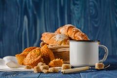 Kop van zwarte koffie in een oude emailmok, ontbijtcroissants o stock fotografie