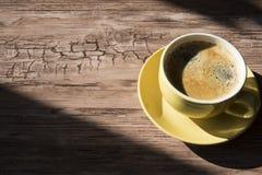 Kop van zwarte koffie in gele mok, tegen houten achtergrond Ruimte voor tekst stock afbeelding