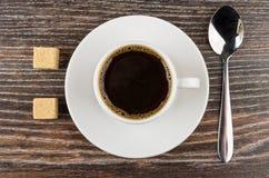 Kop van zwarte koffie op schotel, klonterige suiker en lepel Royalty-vrije Stock Foto's