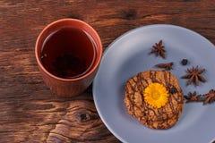 Kop van zwarte thee en chocolade coockies met gele bloem op bovenkant op houten lijst aangaande zwarte achtergrond royalty-vrije stock foto