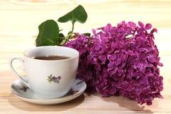 Kop van zwarte thee en tak van seringen op houten achtergrond Royalty-vrije Stock Foto's