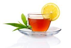 Kop van zwarte thee met citroen en groene bladeren Stock Foto