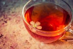 Kop van zwarte thee met de bloem van de kersenboom daarin stock afbeeldingen