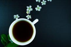 Kop van zwarte thee met kersen hierboven bloemen op zwarte achtergrond van Royalty-vrije Stock Foto's