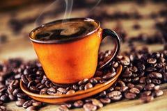 Kop zwarte koffie en gemorste koffiebonen Zoete croissant en een kop van koffie op de achtergrond Stock Afbeeldingen