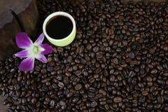 Kop zwarte koffie en koffiebonen op houten achtergrond Stock Foto's